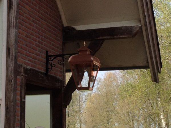 Koperen hanglamp aan sierlijke smeedijzeren muursteun