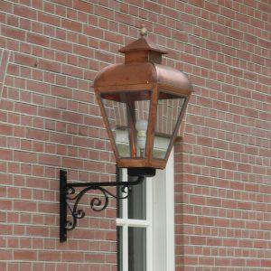 Gevel lamp gemaakt van koper aan een mooi muur met snijvoegen