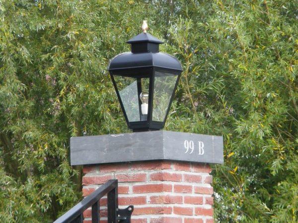 Grote buitenlamop op poort paal.
