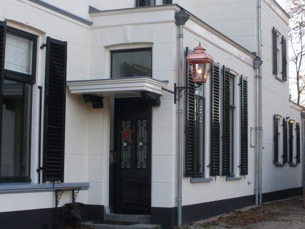 Handgemaakte koperen buitenverlichting aan een victoriaans koloniaal huis