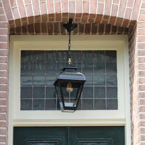 Hanglamp aan ketting zwart in een nis bij de voordeur of onder de veranda