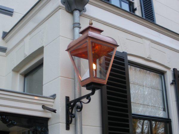 Grote buitenlamp op muursteun aan een momumentaal herenhuis.