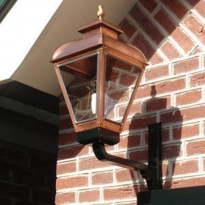 kleine koperen buitenlamp op muursteun