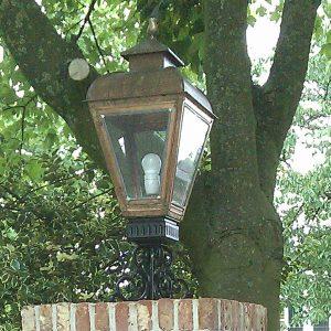 Buitenlamp op voet of sokkel bij een poort