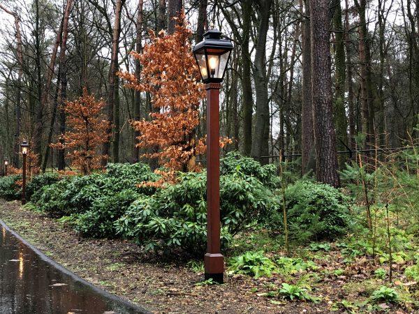 Klassiek lantaarnpaal geplaatst langs een oprijlaan naar een woning.