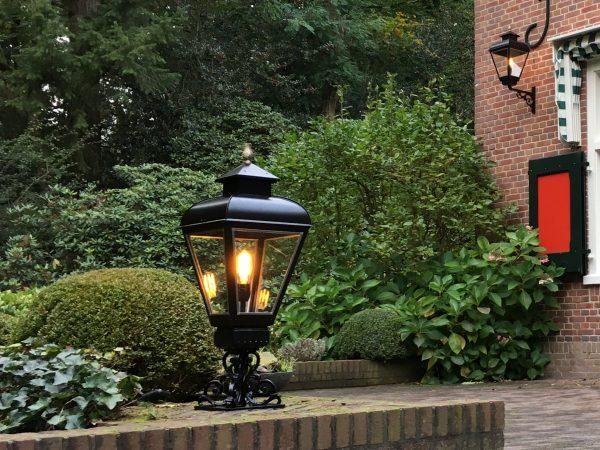 Tuinverlichting op een sokkel op een muurtje in een tuin