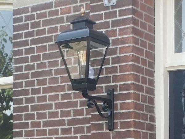 Klassieke buitenlamp aan de gevel naast de deur