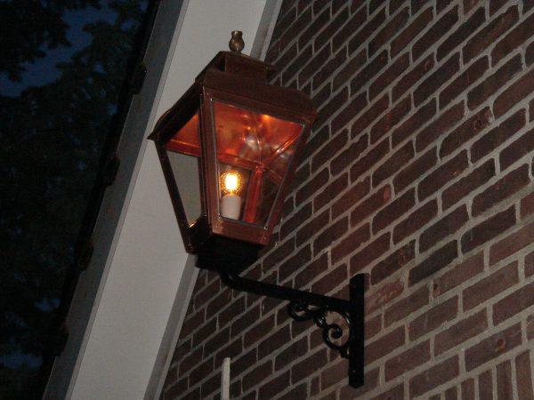 Koperen buitenlamp bij nacht