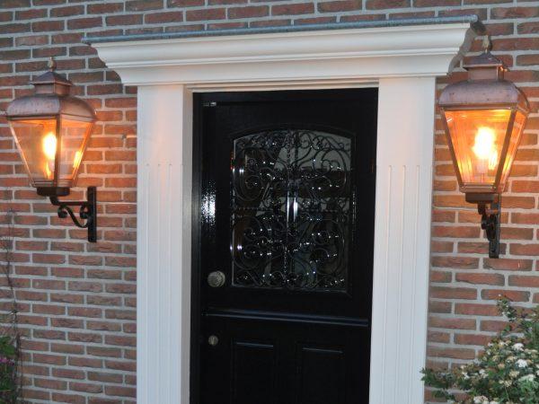 Klassiek koperen buitenlampen bij een mooie voordeur