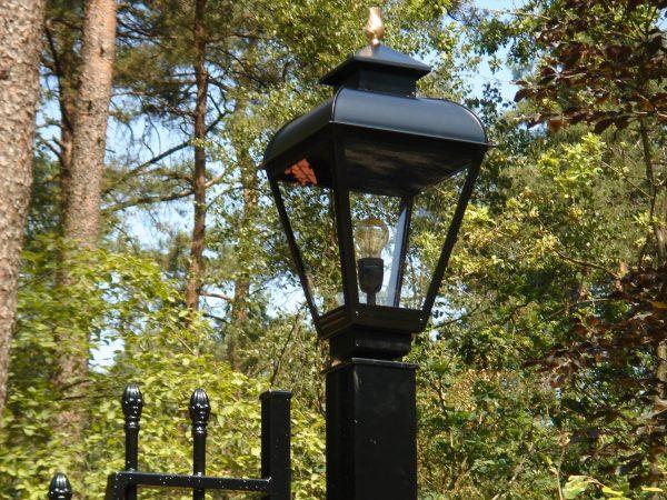 Lamp op hekwerk van een poort of entree.