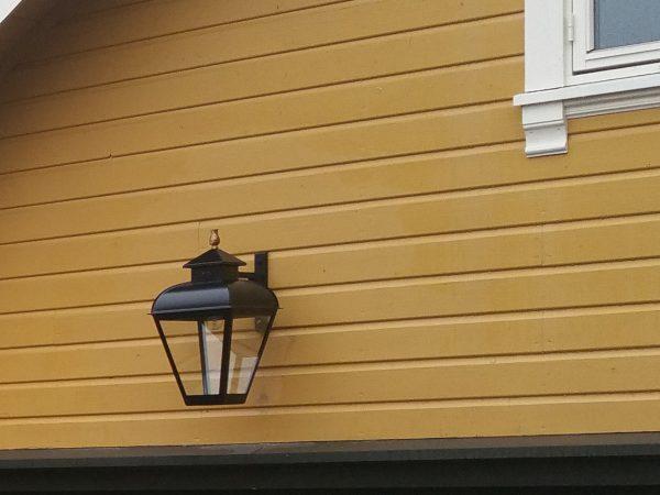 Hier een mooie hangende buitenlamp aan een noorse blokhut