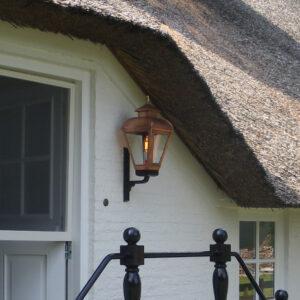 Sfeervolle buitenlamp naarst de deur van een boerderij
