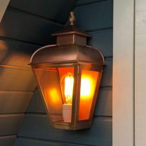 Wandlamp koper met bronzen vlam bovenop hangend aan een saunahuisje.