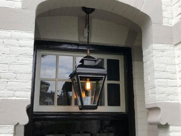 Zwarte hanglamp hangend in een portiek