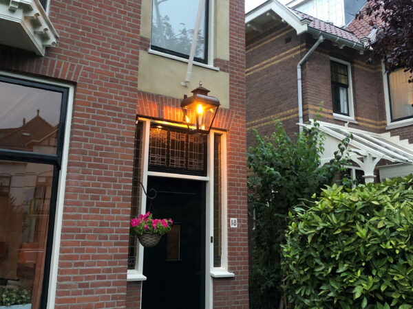 Grote hanglamp aan herenhuis boven de voordeur