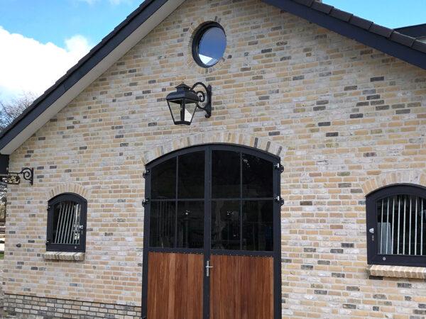 XL hangende lamp boven staldeur van een paardenstal