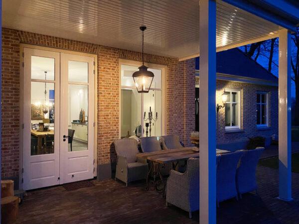 hanglamp aan ketting boven terrastafel onder veranda