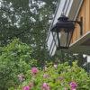 Buitenlamp hangend aan houten huis